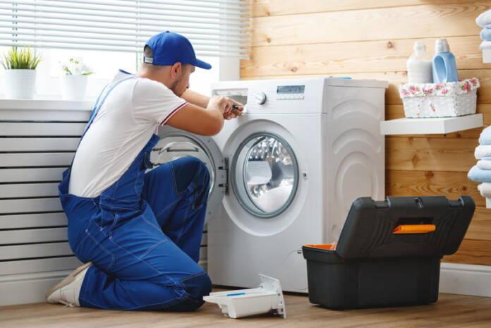 Serwisant naprawiający pralkę